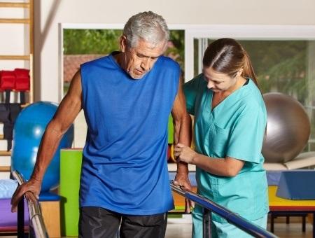 17660215 - senior man doing running training with physiotherapist in nursing home