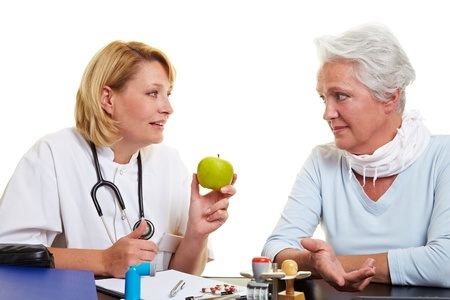 10582313 - doctor recommending a green apple to senior woman