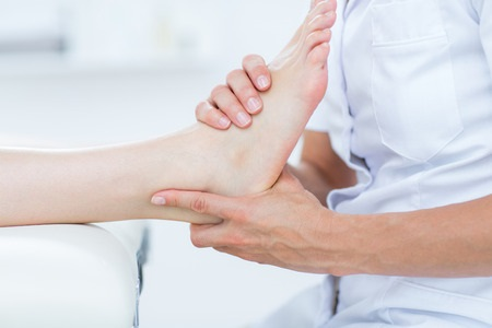 39828280 - physiotherapist doing foot massage in medical office