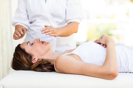 39933111 - calm woman receiving reiki treatment in the health spa
