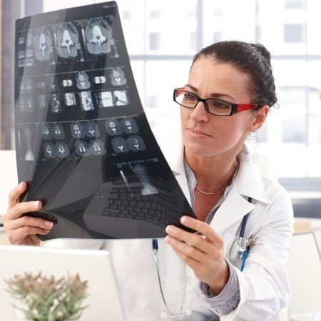 28345386 - portrait of female brunette doctor with x-ray image in hand, wearing glasses, stethoscope and lab coat,