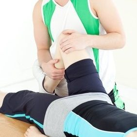 Male physical therapist checking a woman's knee