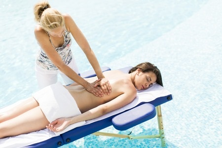 60749901 - young woman having massage at the pool at sunny day