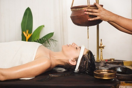 51225614 - caucasian woman having ayurveda shirodhara treatment in india